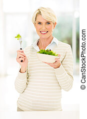 mid age woman eating green salad - happy mid age woman...
