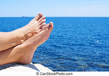relaxing near the ocean - bare feet of a man who is relaxing...