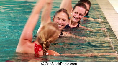 Fit women doing aqua aerobics in th