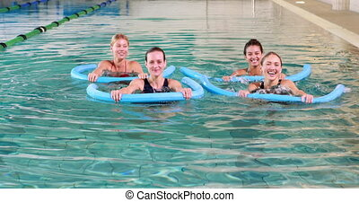 Four women doing aqua aerobics smiling at camera in the...
