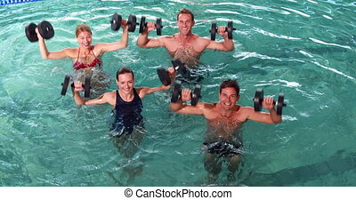 Fit people doing an aqua aerobics class in swimming pool...