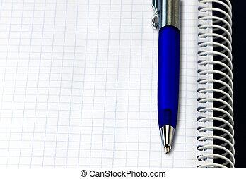 Open spiral notebook with ballpoint pen