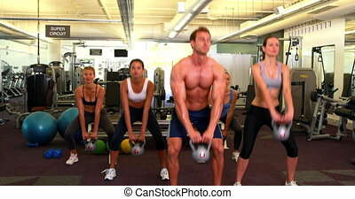 Muscular instructor leading kettlebell class at the gym