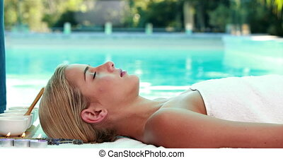 Peaceful blonde lying on massage table poolside outside at...