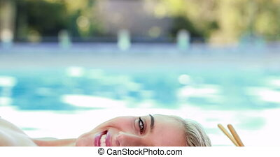 Peaceful smiling blonde lying on massage table poolside...