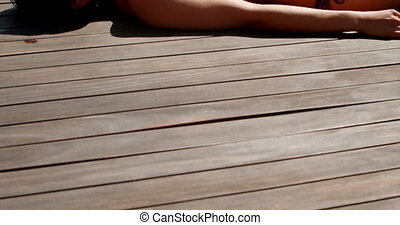 Sexy brunette lying poolside sunbathing on a sunny day