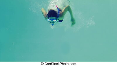 Pretty brunette diving into swimming pool wearing snorkel on...