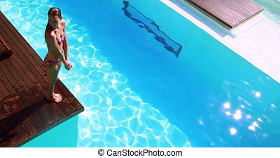 Brunette diving into clear blue pool on her holidays