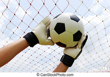 goalkeeper's hands reaching for foot ball - goalkeeper's...