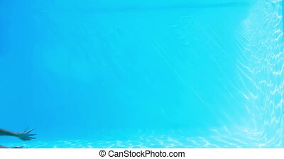 Pretty brunette swimming underwater in pool on her holidays