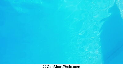 Pretty brunette diving underwater into pool on her holidays
