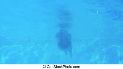 Low angle view of fit swimmer in pool doing front stroke