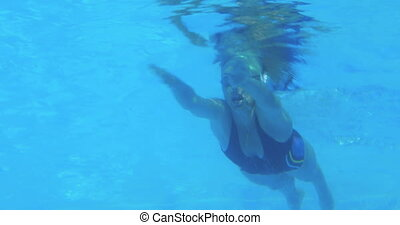 Low angle view of fit swimmer in pool doing breast stroke