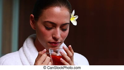 Content brunette drinking herbal tea at the health spa
