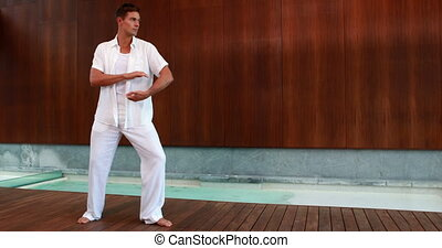 Calm man in white doing tai chi at the health spa