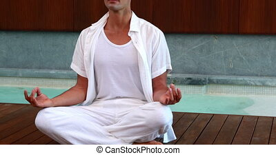 Calm man in white sitting in lotus pose at the health spa