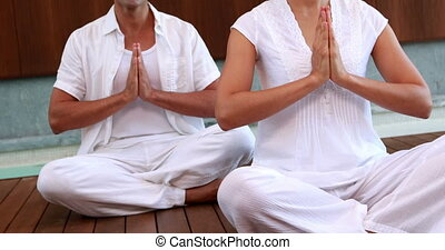 Smiling couple in white sitting in lotus pose with hands...