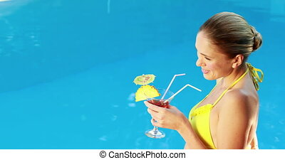 Gorgeous blonde in bikini enjoying a cocktail poolside on a...