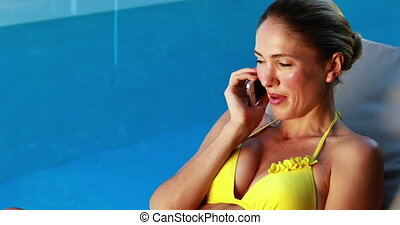 Gorgeous blonde in bikini chatting on phone poolside on a...