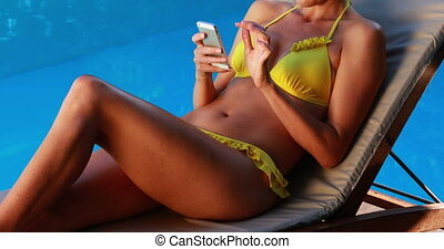 Gorgeous blonde in bikini texting on phone poolside on a...