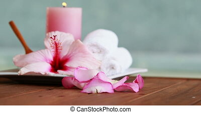 Towels candles and pink flower by the pool at the spa