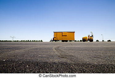 Yellow trailer and a construction machine on a construction...
