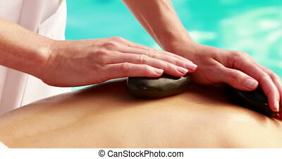 Beauty therapist rubbing womans back with hot stones outside...
