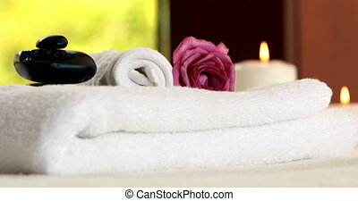 Fresh towels with black stones at luxury spa
