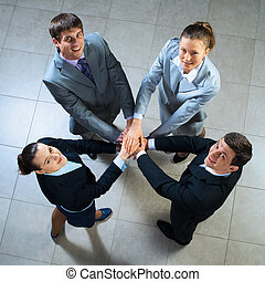 symbol of teamwork - team of four businessmen with folded...