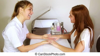 Smiling nail technician examining pretty customers hands at...