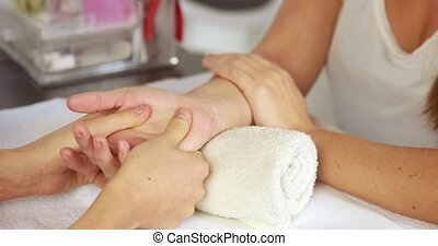 Beauty therapist massaging customers hand at the nail salon