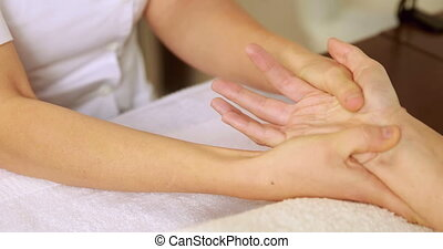 Beauty therapist massaging customers hands at the nail salon