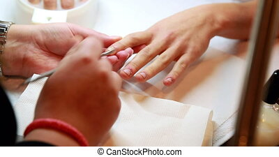 Nail technician giving customer a manicure at the nail salon