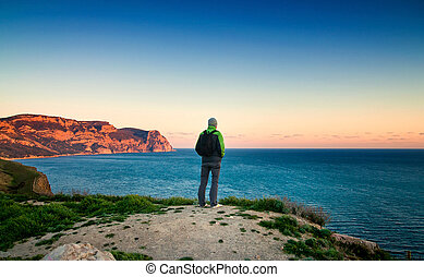 young man stands on a hill at sunset