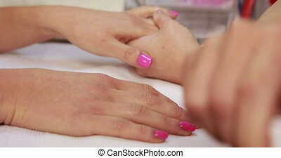 Nail technician applying pink varnish to customers nails at...