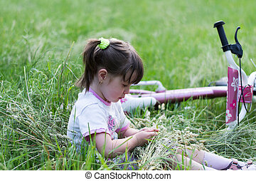 child in grass with bike