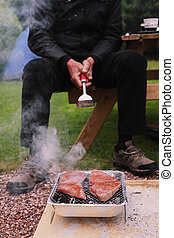 Senior man at barbecue - A senior man is looking after a...