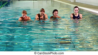 Fit women doing aqua aerobics in the leisure center