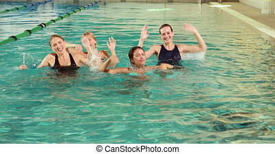 Fit women doing aqua aerobics in the pool in the leisure...