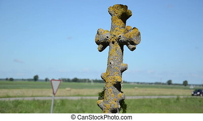 mossy cross car drive - Retro mossy stone cross closeup and...