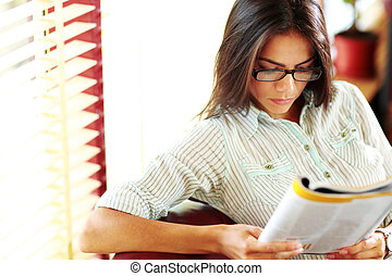 Businesswoman reading magazine in modern office