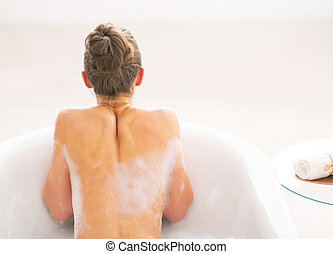 Young woman in bathtub. rear view
