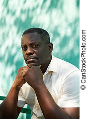 Portrait of middle aged african man staring the camera -...