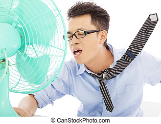 Young man cooling face under wind of fan
