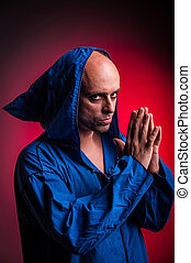 man with evil look with a cassock with hood