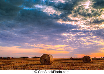 Sunset over farm field with hay bales