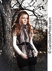 redhead woman in fur coat leaning against old tree at park -...