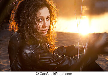 Portrait of brunette curly woman sitting on beach at sunset...