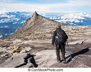 Hiker on Mount Kinabalu, Malaysia - Hiker walking at the top...