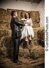 Married couple looking at each other at stable with stack of...